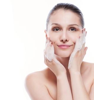 Linda mulher lavando o rosto dela - isolado no branco