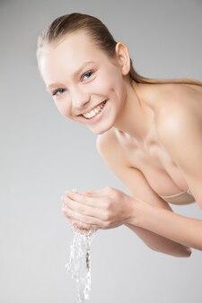 Linda mulher lavando o rosto limpo com água