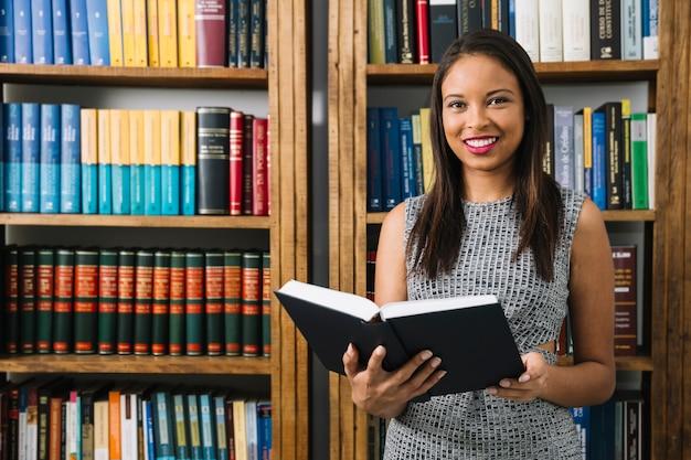 Linda mulher lendo livro na biblioteca