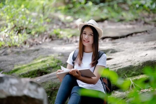 Linda mulher lendo livro na natureza