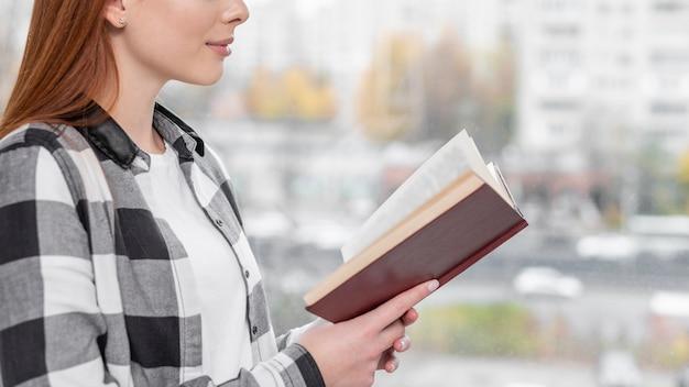Linda mulher lendo livro vista lateral
