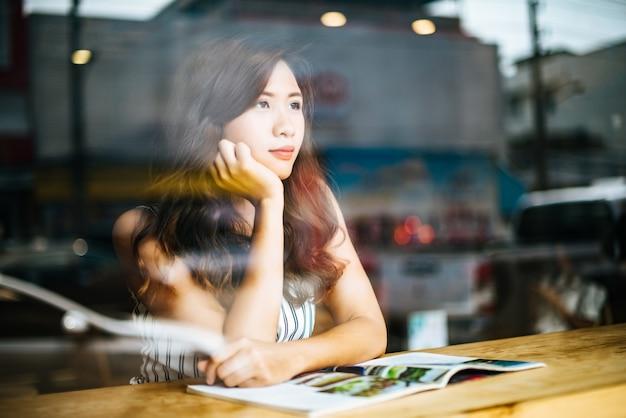 Linda mulher lendo revista no café