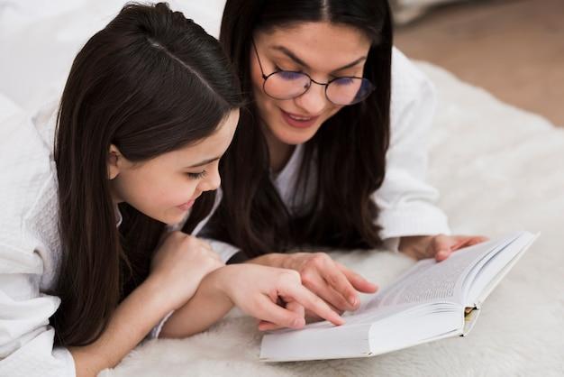 Linda mulher lendo um livro com jovem