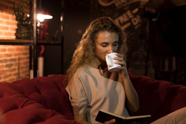 Linda mulher lendo um livro em casa enquanto bebe chá
