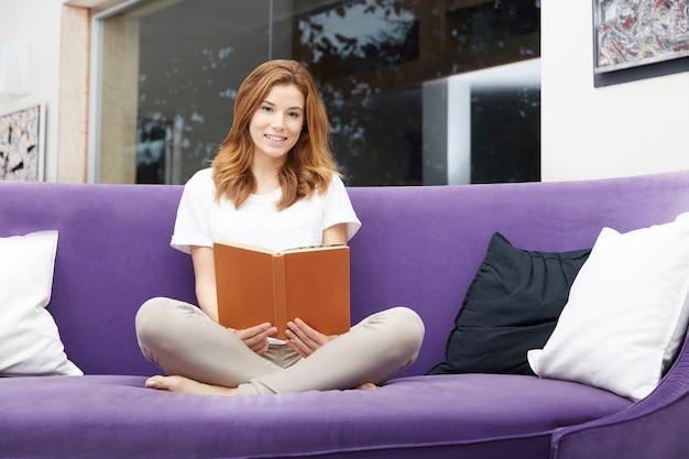 Linda mulher lendo um livro no sofá roxo