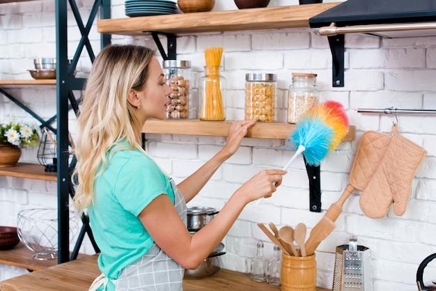 Linda mulher, limpeza de prateleira de cozinha com espanador macio