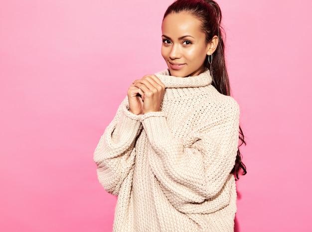Linda mulher linda sorridente. mulher que está na camisola branca à moda, na parede cor-de-rosa.