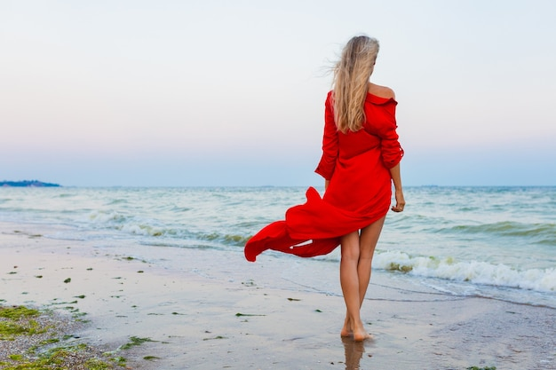 Linda mulher livre vestida de vermelho com o vento na praia do mar, caminhando no verão