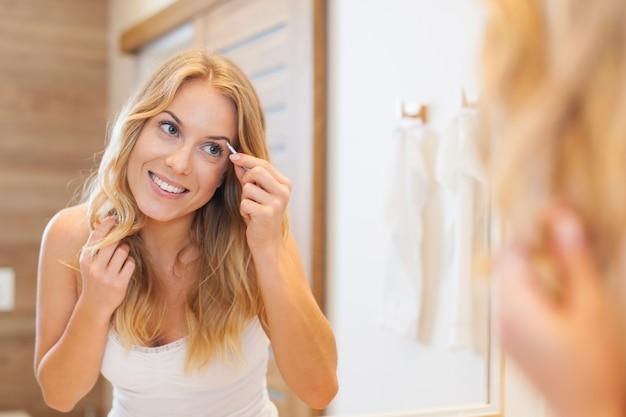 Linda mulher loira a pinçar as sobrancelhas