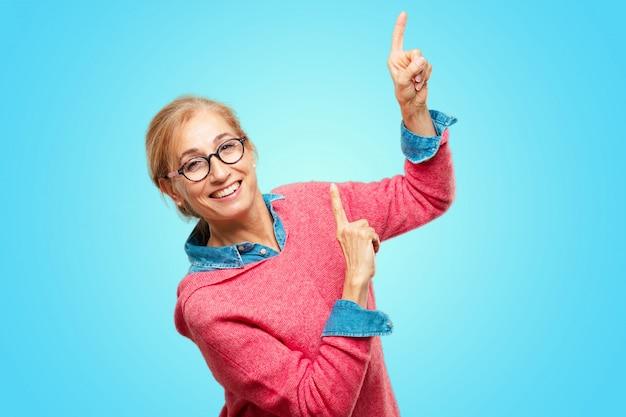 Linda mulher loira adulta sorrindo e dançando a diversão, animada música de discoteca, olhando feliz e em um