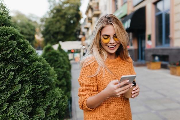 Linda mulher loira andando por arbustos verdes com um sorriso, carregando um smartphone e uma xícara de café