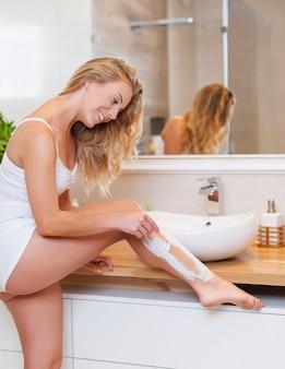 Linda mulher loira barbeando as pernas no banheiro