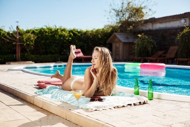 Linda mulher loira bebendo cocktail, banhos de sol, deitado perto da piscina