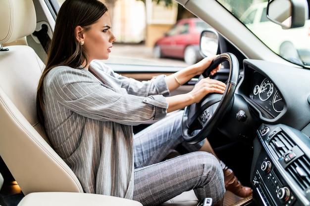 Linda mulher loira buzina no carro em pânico com os olhos fechados enquanto dirige em alta velocidade.