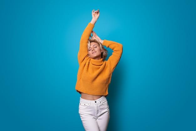 Linda mulher loira caucasiana com suéter amarelo posando com a mão acima na parede azul