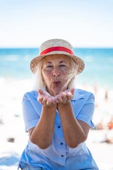 Linda mulher loira caucasiana com um chapéu de palha e uma camisa listrada mandando um beijo no ar, sentada à beira-mar no verão