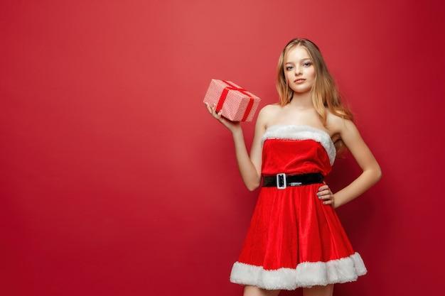 Linda mulher loira caucasiana com vestido de papai noel vermelho sobre fundo vermelho estúdio