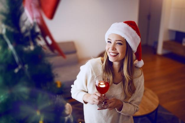 Linda mulher loira caucasiana sorridente com chapéu de papai noel na cabeça, olhando para a árvore de natal e bebendo vinho em pé na sala de estar.