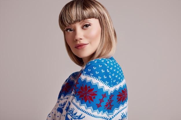 Linda mulher loira com cabelo curto na camisola de natal