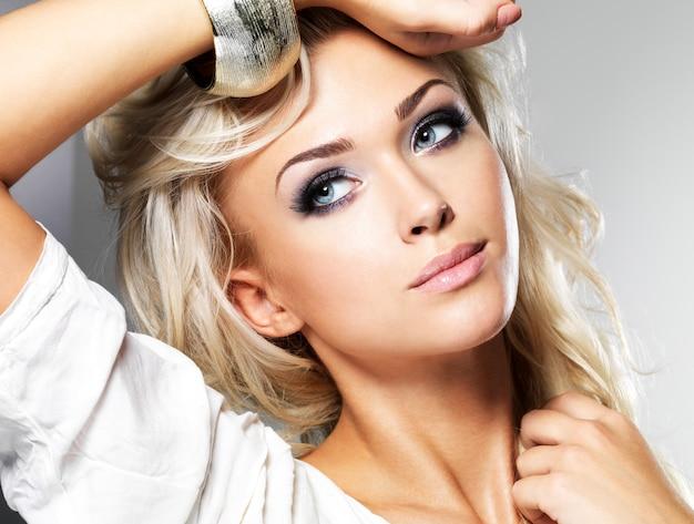 Linda mulher loira com cabelo longo cacheado e estilo de maquiagem. garota posando em estúdio