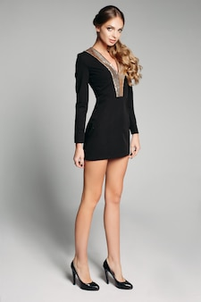 Linda mulher loira com cauda ondulada em mini vestido preto e salto alto.