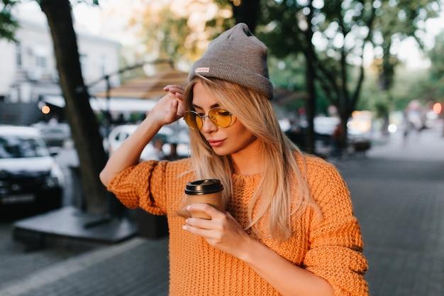 Linda mulher loira com chapéu cinza caminhando para casa após o treino na academia e bebendo café com leite