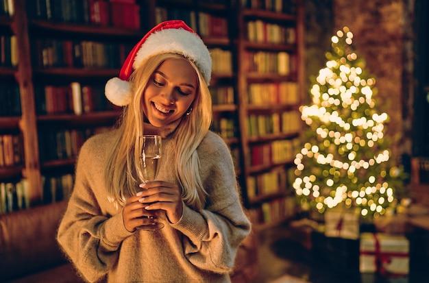 Linda mulher loira com chapéu de papai noel com uma taça de champanhe. no contexto de uma árvore de natal com presentes. feliz ano novo e feliz natal!