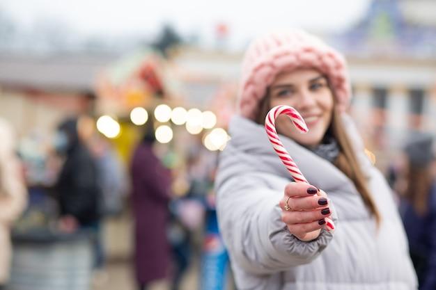 Linda mulher loira com doces em uma feira de natal. espaço para texto
