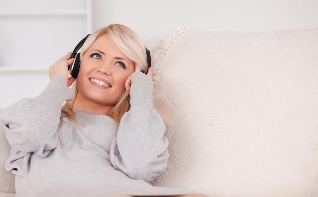 Linda mulher loira com fones de ouvido deitado em um sofá