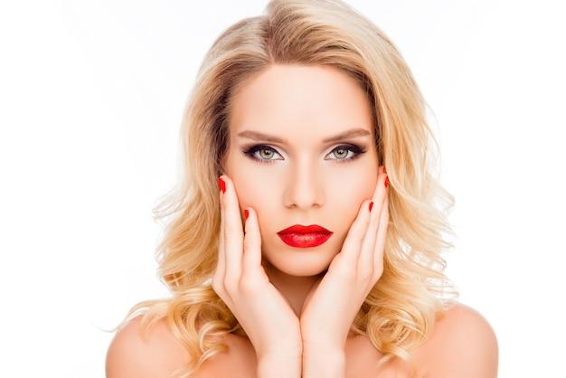Linda mulher loira com lábios vermelhos e manicure tocando seu rosto