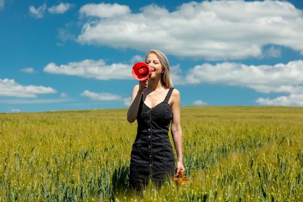 Linda mulher loira com mala e megafone no campo de trigo em dia de sol