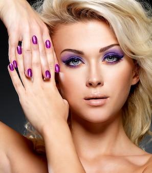 Linda mulher loira com manicure de beleza roxa e maquiagem dos olhos. modelo com penteado encaracolado.