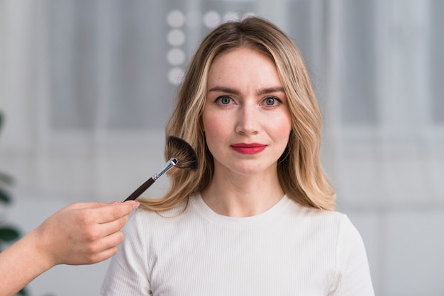Linda mulher loira com maquiagem no salão de beleza