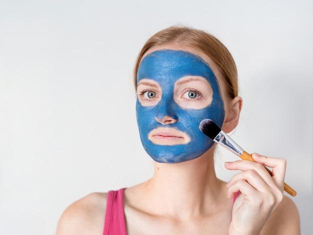 Linda mulher loira com máscara facial de argila azul aplicar pela esteticista.
