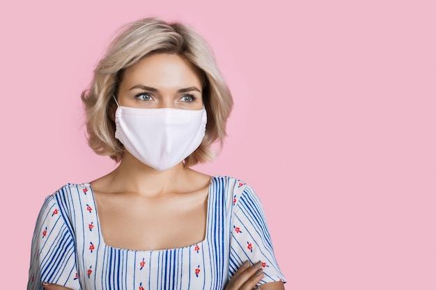 Linda mulher loira com máscara médica no rosto, posando em uma parede rosa do estúdio com espaço livre usando um lindo vestido