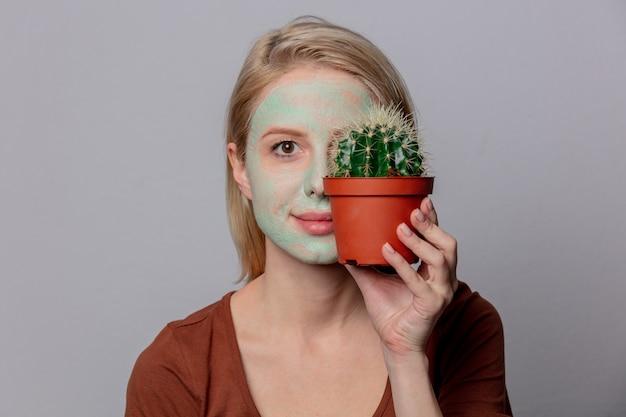 Linda mulher loira com máscara verde e cacto