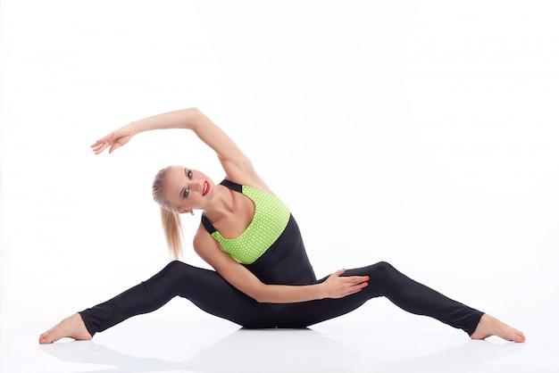 Linda mulher loira com roupa de esportes, aquecendo o alongamento, sentado no chão