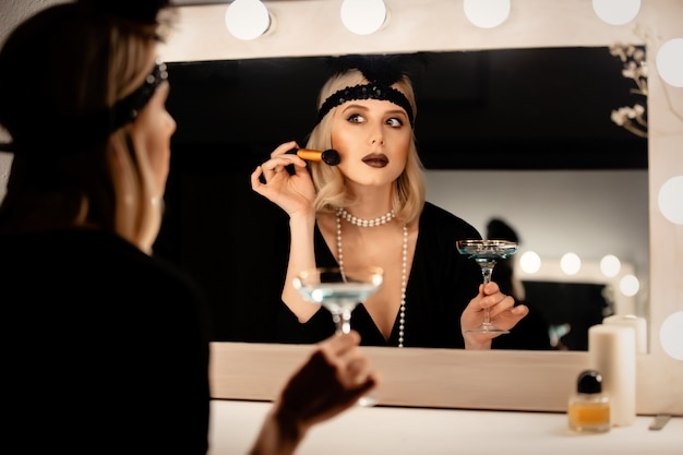 Linda mulher loira com roupas de vinte anos aplicar maquiagem perto de um espelho com lâmpadas