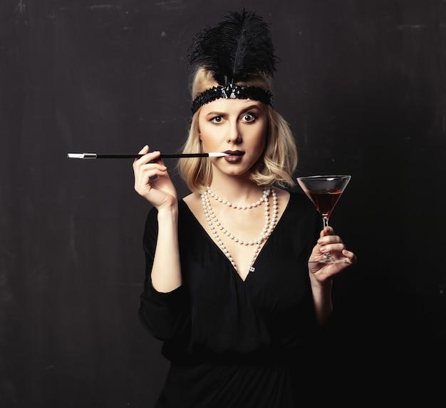 Linda mulher loira com roupas de vinte anos com cachimbo e coquetel em fundo escuro