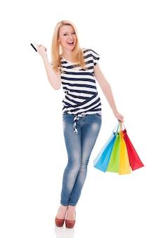 Linda mulher loira com sacolas de compras e cartão de crédito