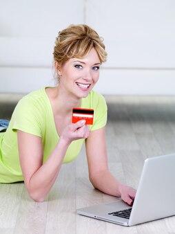 Linda mulher loira com um sorriso feliz segurando um cartão de crédito e usando o laptop - dentro de casa
