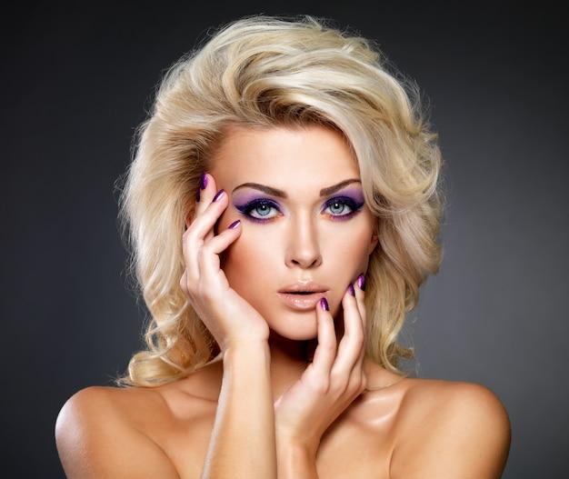 Linda mulher loira com uma bela manicure roxa e maquiagem nos olhos