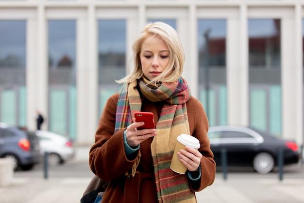 Linda mulher loira com uma xícara de café usando telefone celular