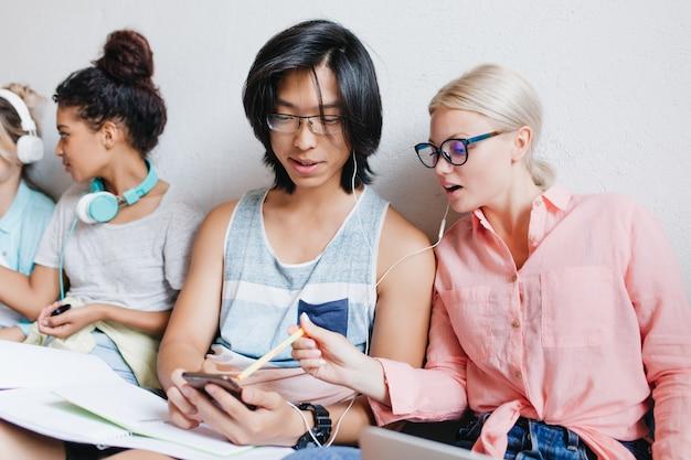 Linda mulher loira de óculos apontando com lápis para a tela do telefone enquanto ouve música com o cara asiático. alunos alegres, aprendendo juntos e se divertindo na faculdade.