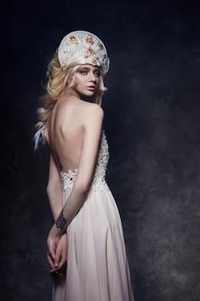 Linda mulher loira de vestido com as costas nuas e uma tiara na cabeça dela