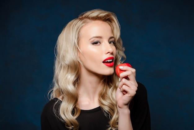 Linda mulher loira de vestido preto, segurando a maçã