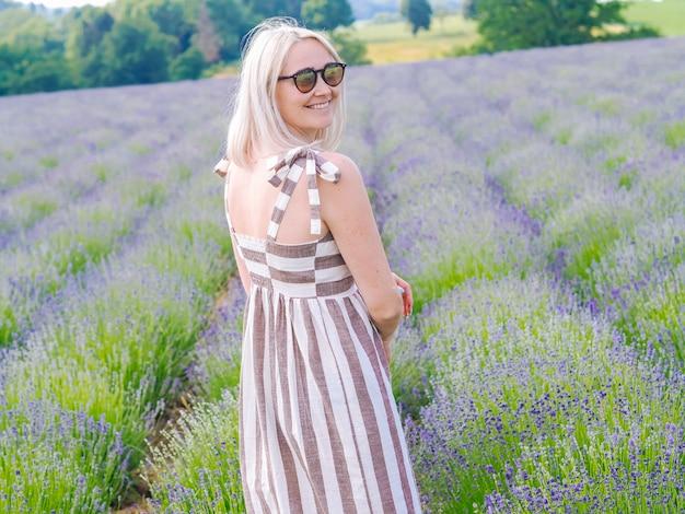 Linda mulher loira de vestido sente-se entre os campos de lavanda em provence. campos de violeta lavanda florescendo na luz solar do verão. paisagem de mar de flores lilás. ramo de flores perfumadas da provence francesa