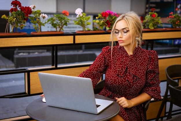 Linda mulher loira de vestido vermelho e óculos, sentada em um café na rua com um laptop