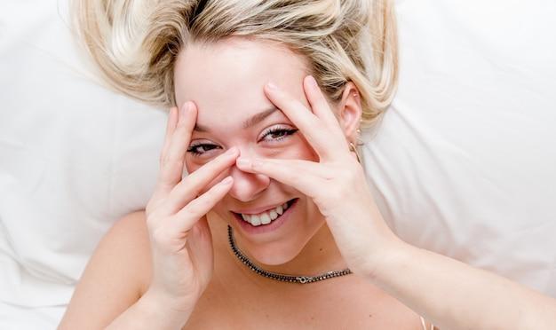 Linda mulher loira deitada na cama cobrindo o rosto com as mãos