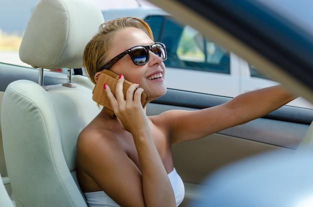 Linda mulher loira dirigindo seu carro conversível